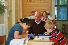Herr Wolfgang Köster mit Kindern beim Hausaufgaben machen